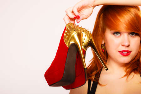 spiked: Shopaholic, fashion and women style. Shopping time. Young red haired female holding high heeled shoes in hands on pink background. Studio shot. Stock Photo