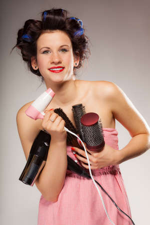 Young woman preparing for date having fun, cute girl with curlers styling hair with many accessories comb brush hairdreyer on  gray photo