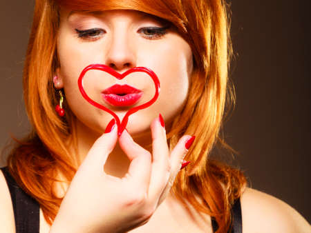 red haired woman: Woman falling in love. Valentines Day concept. Attractive young red haired woman making heart symbol in hands on brown background. Studio shot. Stock Photo