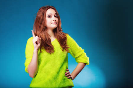 Young serious woman shaking wagging her finger teenage girl scolding on blue Stock Photo