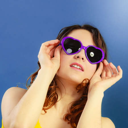 Summer fashion eyes protection concept. Closeup girl long curly hair in violet heart shaped sunglasses on blue photo