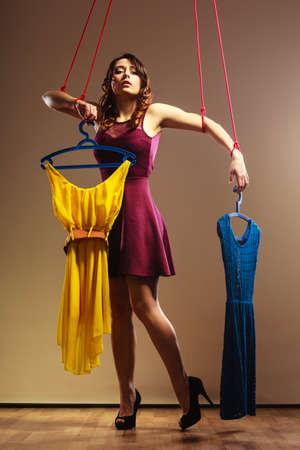 compras compulsivas: Shopaholic concepto de adicci�n de la moda. Adicto a la mujer de las compras, chica marioneta con ropa en cadena, la compra de trastorno.