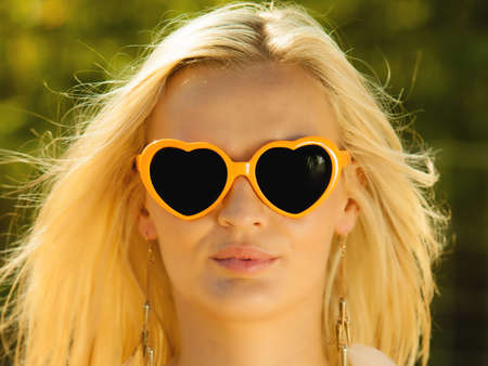 Holidays, vacation and summer fashion concept. Closeup attractive blonde girl in orange heart shaped sunglasses outdoor photo