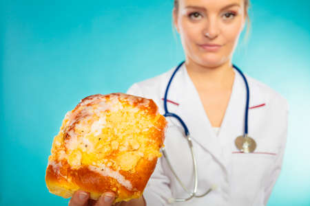 interdiction: Unhealthy nutrition overweight concept. Nutritionist saying no to sugary dessert. Woman doctor dietician holding sweet bun recommending non sugar diet on blue