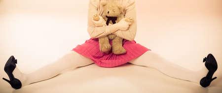 puppet woman: Concepto de trastorno mental. Mujer joven que llevaba de ni�o como mu�eco t�tere sosteniendo oso de peluche foto de estudio juguete