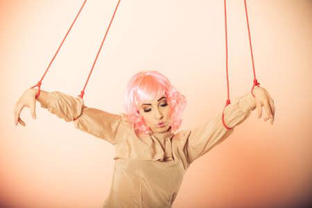 manipulate: Young woman girl stylized like marionette puppet on string