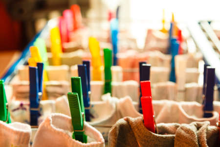 laundry line: Housework concept. Closeup clothes hanging to dry on a laundry line with colorful pegs clips indoor