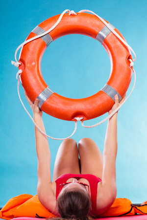Accident prevention and water rescue. Woman holding life buoy ring lifebelt studio shot blue background photo