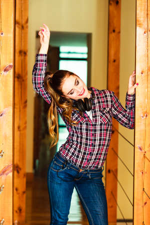 Music and technology concept - smiling teenage girl wearing jeans plaid shirt with headphones listening mp3 dancing at home photo