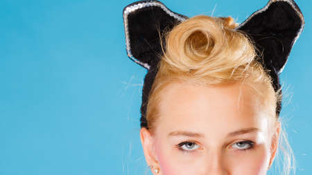 coiffure: Pin up and retro style coiffure. Blonde woman part face with hairdo black ears on head on blue background in studio.