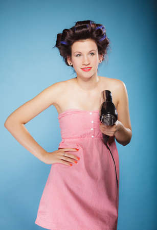 coif: Young woman preparing to party having fun, funny girl styling hair with hairdreyer retro style on blue
