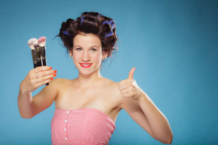 hair rollers: Cosmetic beauty procedures and makeover concept. Woman in hair rollers holding makeup brushes set making thumb up gesture on blue