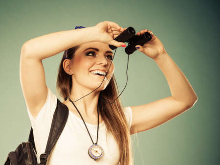 Summer holidays and tourism concept. Lovely tourist woman with backpack compass looking through binoculars filtered photo photo