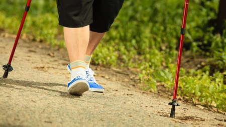 persona caminando: estilo de vida madura activa. nordic walking de alto nivel en un parque rural