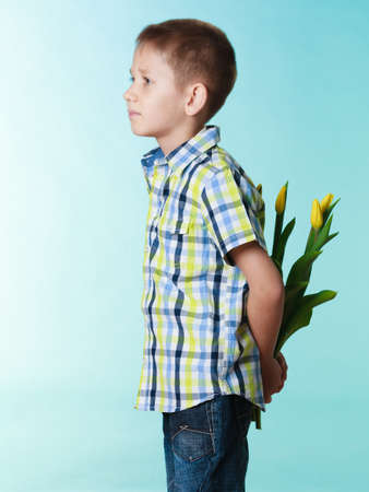 Holiday mothers day concept. Little boy has prepared surprise present for mum, flowers yellow tulips, holds it behind the back on blue photo