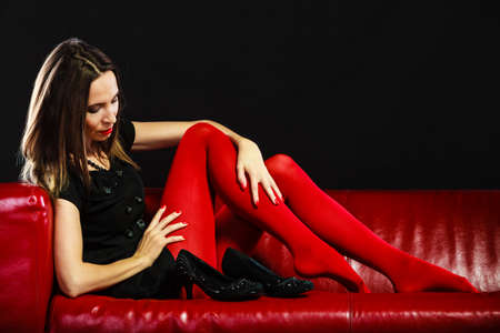expensive: Elegance and fashion outfit. Fashionable woman legs in red vivid color tights posing on couch black background Stock Photo