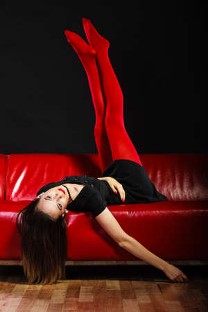 Elegance and fashion outfit. Fashionable woman legs in red vivid color tights posing on couch black background photo