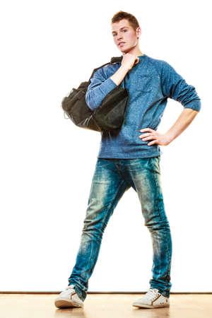 Jeune homme à la mode garçon adolescent en pleine longueur des jeans de style décontracté détenant sac noir isolé sur blanc