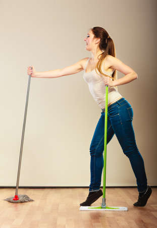 charwoman: Cleanup housework concept. Funny cleaning lady young woman mopping floor, holding two mops new and old dancing