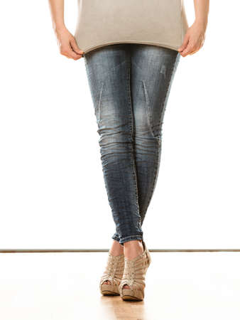 denim trousers: Fashion and people concept. Woman legs in denim trousers platform high heels shoes casual style isolated on white background Stock Photo