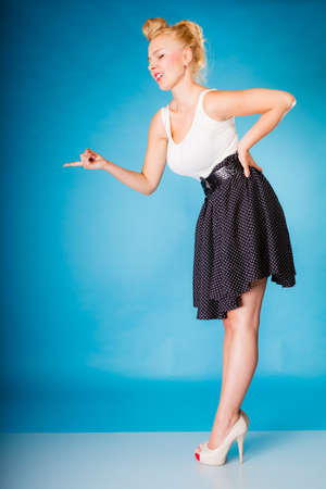 wagging: Sexy retro girl full length. Pin up woman with blonde hairdo and shaking wagging her finger gesture sign on blue background in studio.