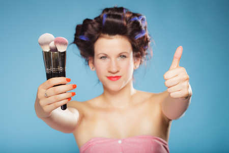 rollers: Cosmetic beauty procedures and makeover concept. Woman in hair rollers holding makeup brushes set making thumb up gesture on blue