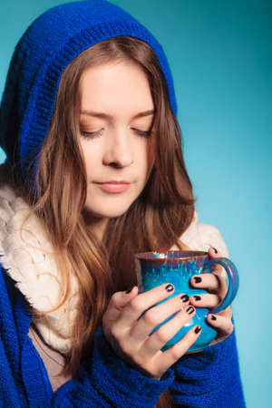 teenage girl: Hot beverage. Closeup teen girl holding blue mug with drink tea or coffee. Woman warming herself