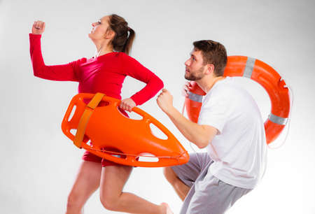 life belt: Accident prevention and water rescue. man and woman lifeguard couple on duty running with with life belt lifesaver equipment on gray