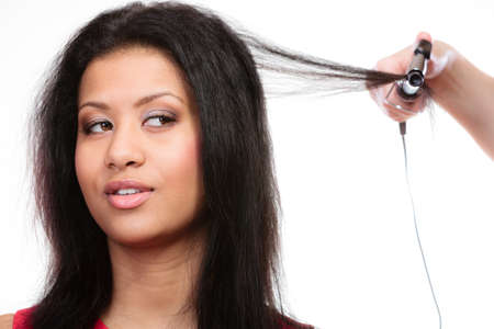 hair dresser: Hairstyling. attractive mixed race woman with long hair making hairstyle hairdo with electric hair curler iron on white Stock Photo