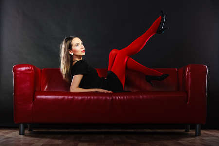 Elegant fashion outfit. Fashionable woman long legs in red vivid color pantyhose posing on couch indoor on black photo