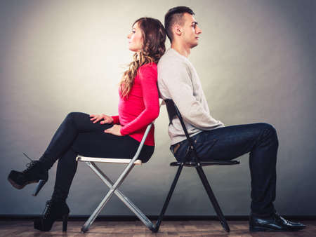 Bad relationship concept. Man and woman in disagreement. Young couple after quarrel sitting on chairs back to back photo