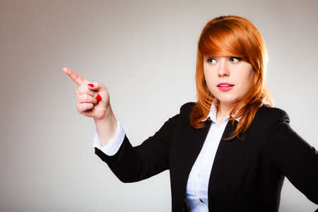 pointing at: Advertisement concept - redhead business woman pointing with finger showing blank copy space on gray