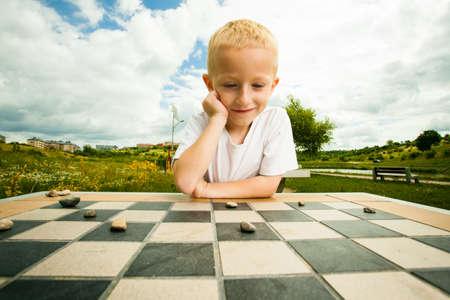 Damas juego de mesa. El niño pequeño chico niño inteligente jugando a las damas de pensamiento, al aire libre en el parque. Infancia y desarrollo Foto de archivo