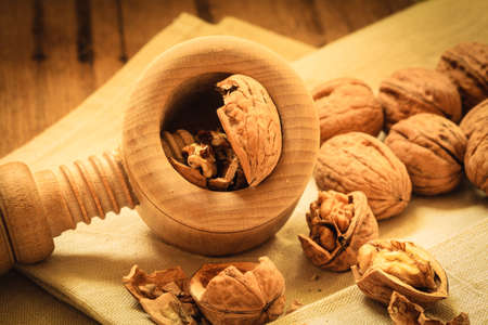 acids: Healthy food full of omega-3 fatty acids, organic nutrition. Walnut with nutcracker on rustic old table Stock Photo