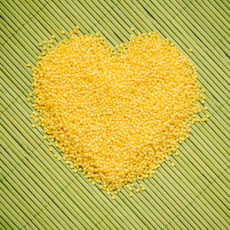 non: Dieting healthcare concept. Millet groats heart shaped on green straw mat surface. Healthy food non gluten grain.