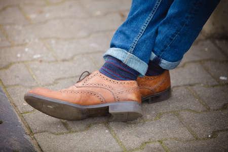 calcetines: La moda de oto�o, desgaste del pie. Piernas masculinas en pantalones vaqueros y botas calcetines a rayas al aire libre en la calle Foto de archivo