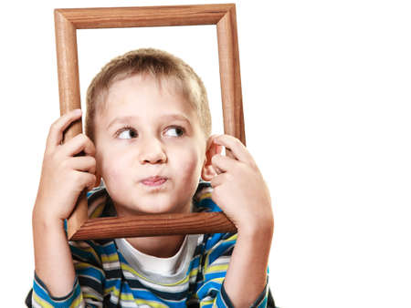 looking in corner: Portrait of little funny blonde boy child holding photo frame framing his face looking into the corner studio shot isolated on white