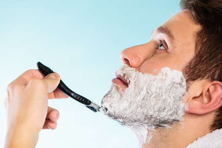 skin care: Health beauty and skin care concept. Closeup young bearded man with foam on face shaving with razor on blue background.