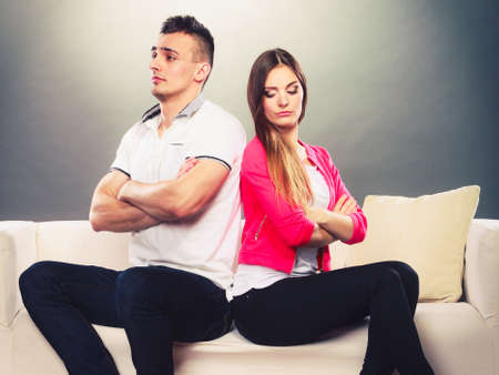 sullenly: Bad relationship concept. Man and woman in disagreement. Young couple after quarrel sitting on sofa back to back Stock Photo