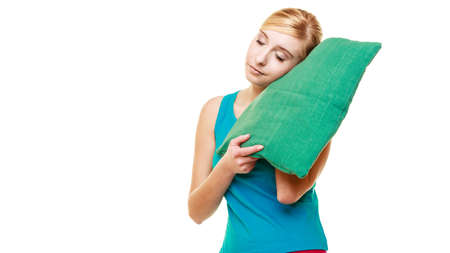 slumber: Health balance sleep deprivation concept. Sleepy tired teen girl with green pillow almost falling asleep. female student with lack of slumber isolated over white background