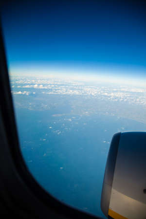 birds eye: Blue white cloudy sky and engine. View from window of airplane flying in clouds. Skyscape cloudscape. Birds eye.