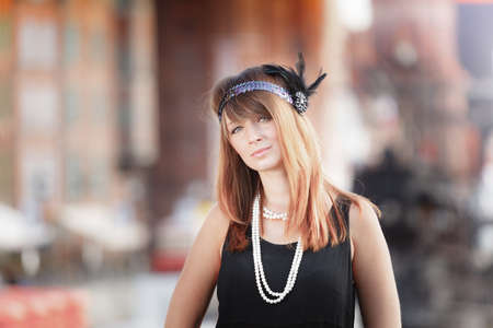 string of pearls: Flapper girl portrait. Retro style fashion vintage woman from roaring 1920s in headband with string of pearls, outdoor. City background Stock Photo