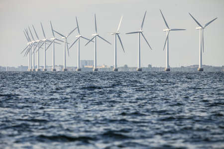 wind turbines power generator farm for renewable energy production along coast baltic sea near Denmark. Alternative green energy ecology.