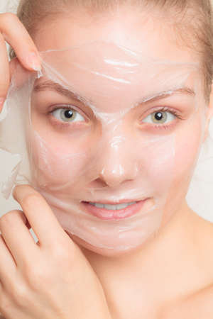 face off: Beauty skin care cosmetics and health concept. Closeup young woman face, girl removing facial peel off mask on gray. Peeling
