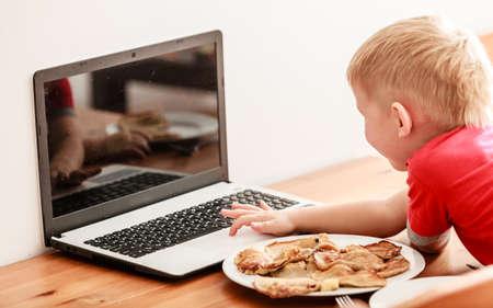 malos habitos: Los ni�os, la tecnolog�a y el hogar concepto - ni�o peque�o ni�o comiendo comida mientras se utiliza el equipo de PC port�til en casa. Malos h�bitos Foto de archivo