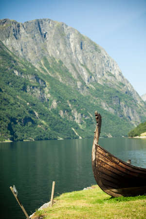 sognefjord: Tourism and travel. Mountains and fjord Sognefjord in Norway, Scandinavia. Old viking boat ship on seashore.