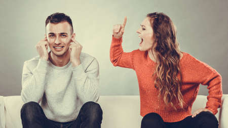 relationship problems: couple having argument - conflict, bad relationships. Angry fury woman screaming man closing his ears.