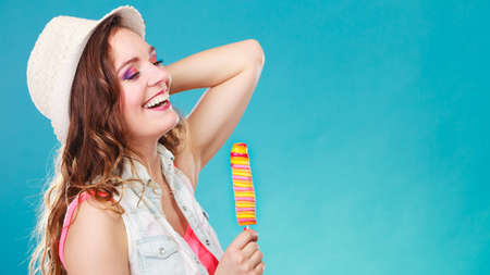 woman fashionable: Summer vacation happiness concept. Smiling joyful and cheerful woman fashionable female model eating ice pop on blue background