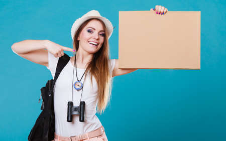 Summer tourism active lifestyle concept. Woman happy female tourist hitchhiking with blank sign cardboard on blue photo