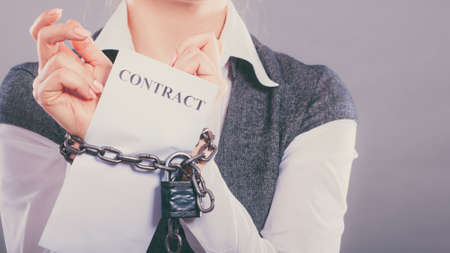 slave labor: Business concept. businesswoman with chained hands holding contract Stock Photo